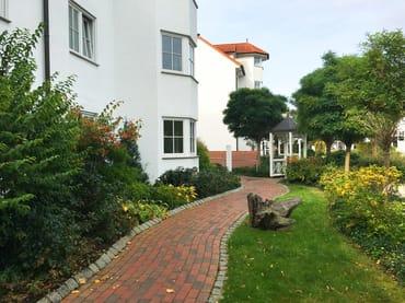 Der Zugang zu Ihrer Wohnung mit sehr gepflegten Grünanlagen.