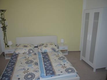 Schlafzimmer 1 im EG mit Doppelbett und Schrank, Durchgang zu SZ 2