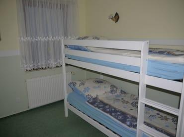 Schlafzimmer 2 im EG mit Etagenbett, Durchgang zu SZ 1