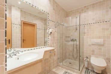 Exklusives Bad mit niedrigem Duscheinstieg und großem Spiegel