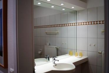 Badezimmer mit Dusche und großem Wandspiegel