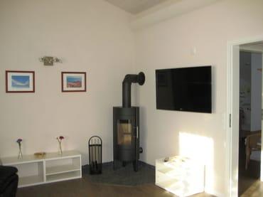 Kamin und Fernsehbereich im Wohnzimmer mit Blick ins Kinderschlafzimmer