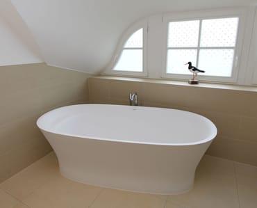 Im Obergeschoss befindet sich ein großzügiges Badezimmer mit freistehender Badewanne, Dusche und WC.