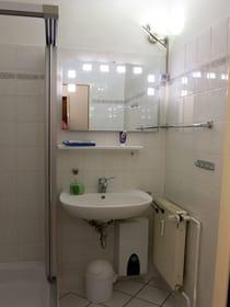 Bad mit Dusche, Handwaschbecken und WC