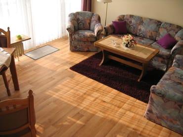 Wohnzimmer mit Sitzecke und ausziehbarer Schlafcouch