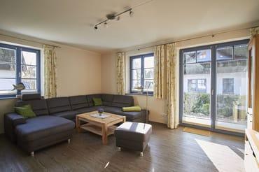 Das Wohnzimmer ist hell und lichtdurchflutet. Die große bequeme Kuschelcouch sorgt für Entspannung und Bequemlichkeit.