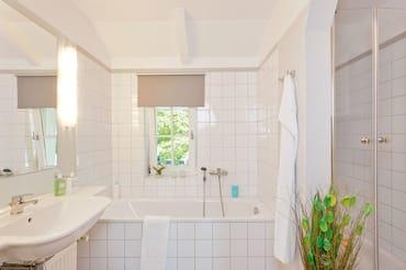 Das Badzimmer mit Fenster ist mit Badewanne, Dusche, WC, Haarfön ausgestattet.