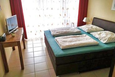 Schlafzimmer mit Doppelbett-Boxspringmatratzen und TV