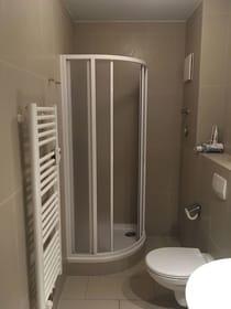 gefliestes Bad mit WC, Dusche, Fön, Duschgel, Handseife und Toilettenpapier