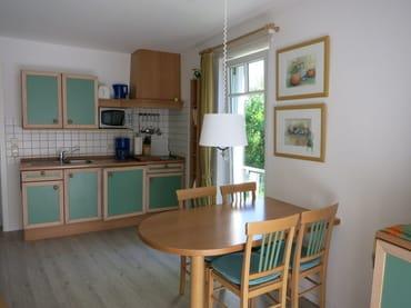 In den Wohnbereich harmonisch integriert ist eine komplett eingerichtete Küchenzeile. Durch das raumhohe Seitenfenster schaut man ins Grüne u. in den Frühjahrs- und Wintermonaten sogar auf das Meer.