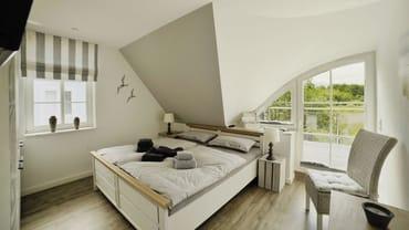Schlafzimmer 1 mit Doppelbett und Balkon im OG