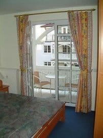 Schlafzimmer mit bequemem Doppelbett und Balkon