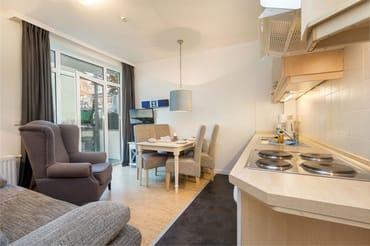 Das Wohnzimmer mit TV, WLAN und Küchenzeile hat einen Austritt zum Balkon.