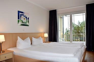 Schlafzimmer mit Doppelbett & Zugang auf den Balkon