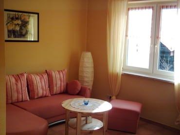 Wohnraum mit ausziehbarer Couch, Fernseher und Radio