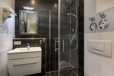 Das schicke Bad hat Echtglasdusche, WC und Fön.