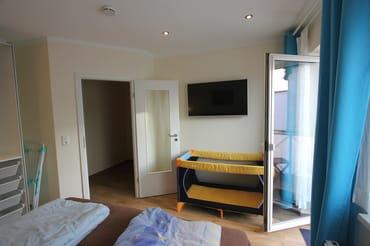 Schlafzimmer mit Fernseher, Babybett und Ausgang Balkon