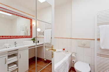 Das an das Schlafzimmer angrenzende Badezimmer verfügt über eine Badewanne, ...