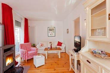 Der helle Wohnbereich ist mit bequemer Couch und einem Sessel ausgestattet und lädt zum Entspannen vor dem Flat-TV oder dem Kamin ein.