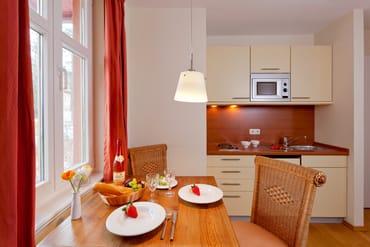 Neben zwei Kochplatten und einem Kühlschrank mit Gefrierfach finden sich auch ein Wasserkocher, ein Toaster sowie eine Kaffeemaschine.