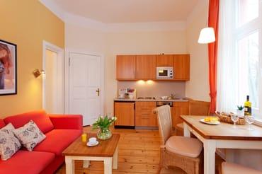 Der großzügige Wohnraum ist mit Flat-TV sowie bequemen Polstermöbeln ausgestattet.