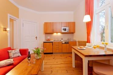 In den Wohnraum ist eine Küchenzeile integriert, die mit allem (Kochfeld, Geschirrspüler, Kühlschrank mit Gefrierfach, Kaffeemaschine, Wasserkocher, Toaster)  ausgestattet ist.