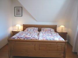 Schlafzimmer mit begehbarem Kleiderschrank, Sekretär und TV