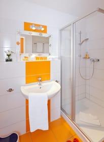 Das Badezimmer ist mit Dusche, WC, Handtuchtrockner und Fußbodenheizung ausgestattet.