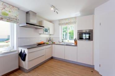 Die im Wohnbereich integrierte komplett ausgestattete Einbauküche ...
