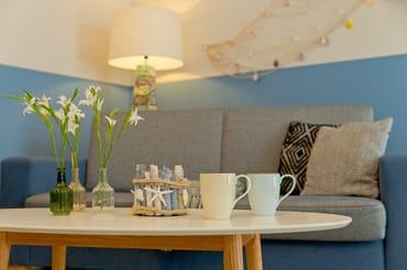 Der Wohnbereich verfügt über eine gemütliche Couch (Die bequeme Couch kann mit wenigen Handgriffen zu einem Schlafplatz für zwei Gäste umgewandelt werden.) ...