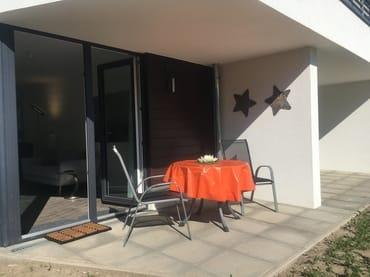 Die Terrasse mit Möbeln und Sonnenschirm