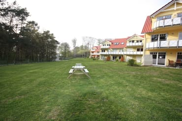 Rasenanlage mit Grillplatz hinter dem Haus, links der Küstenwald