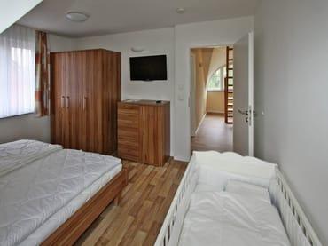 Schlafzimmer mit Kinderbett, Flachbild-TV