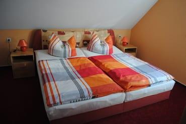 Schlafzimmer mit Doppelbett und Platz für Babybettchen
