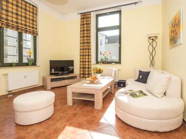 Der Wohnraum ist mit einer bequemen Sitzgarnitur und Flat-TV ausgestattet, sodass Sie sich zu gemütlichen Stunden nach einem erlebnisreichen Urlaubstag in Ihr Feriendomizil zurückziehen können.