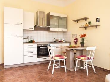 Die integrierte Küchenzeile bietet beste Voraussetzungen für die Zubereitung Ihrer Speisen (Geschirrspüler, Kühlschrank, Cerankochfeld, Backofen, Mikrowelle, Wasserkocher, Toa