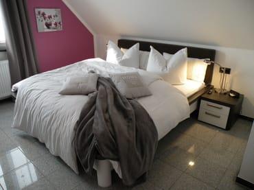 Gemütliches Schlafzimmer unter Dachschrägen, mit TV, großer Schrank mit viel Stauraum, Ganzkörperspiegel, Sessel, Reisebett. Komplett verdunkelbar