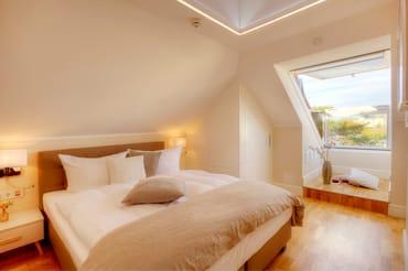 Über eine Treppe gelangen Sie in den oberen Bereich der Suite, wo zwei weitere Schlafzimmer mit jeweils Doppelbett, TV sowie ein Gäste-WC auf Sie warten.