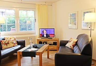 gemütliches helles Wohnzimmer mit LED-TV, Blu-ray-Player, Radio, CD-Spieler