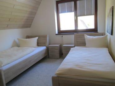 Schlafzimmer 1 mit Einzelbetten und TV