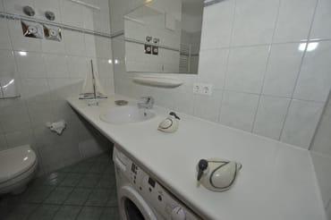 blick ins Badezimmer mit Waschmaschine, Dusche und Badewanne