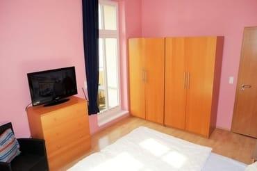 Schlafzimmer mit Doppelbett, großer Flachbild - TV und Zugang zum Eckbalkon