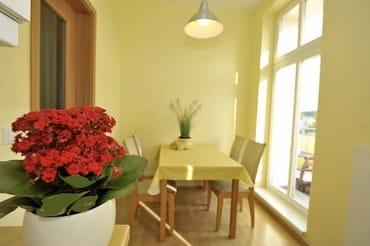 Blick zur separaten Essecke in der sonnigen Küche mit großer Balkontür