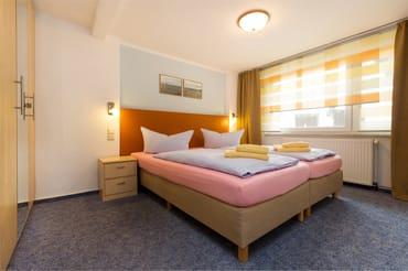 Das Schlafzimmer hat Doppelbett, Kleiderschrank und Verdunkelungsgardinen.