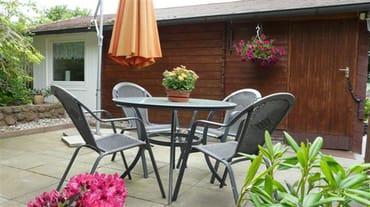 Zum Ferienhaus gehört eine möblierte Terrasse.