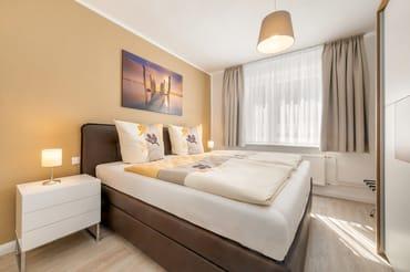 Schlafzimmer 1 hat ein bequemes Boxspringbett von Ruf (180x200cm), TV und einen großen Kleiderschrank.