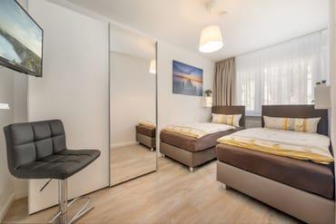 Schlafzimmer 2 hat 2 Einzelbetten, TV und Kleiderschrank. Fenster ebenfalls mit Verdunkelungsgardinen und Mückenschutzgitter.