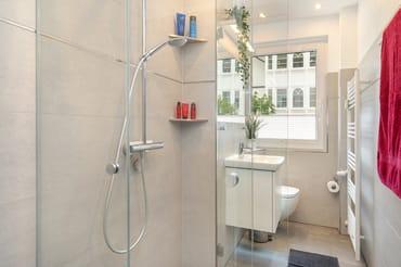 Das moderne Bad mit Regendusche und WC. Die Dusche ist bodengleich.