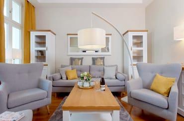 In dem großzügigen Wohnbereich wartet eine einladende Sitzecke mit Couch und zwei Sesseln, Flat-TV  u.v.m. zum Entspannen auf Sie.