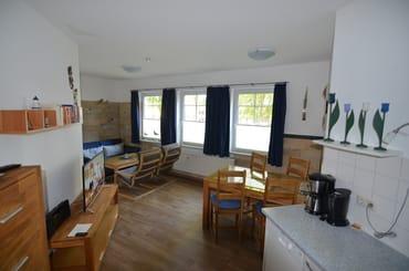 Wohnzimmer mit großem Esstisch, zwei Relaxsesseln und Couch